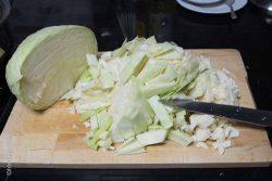 Beim Weißkohl den Strunk entfernen und den Kohl in mittelgrobe Streifen schneiden